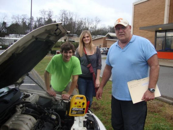 Special to the News Sentinel Teacher David Moore, right, recently jump started the vehicle of siblings Jordan and Jennifer McKenzie.